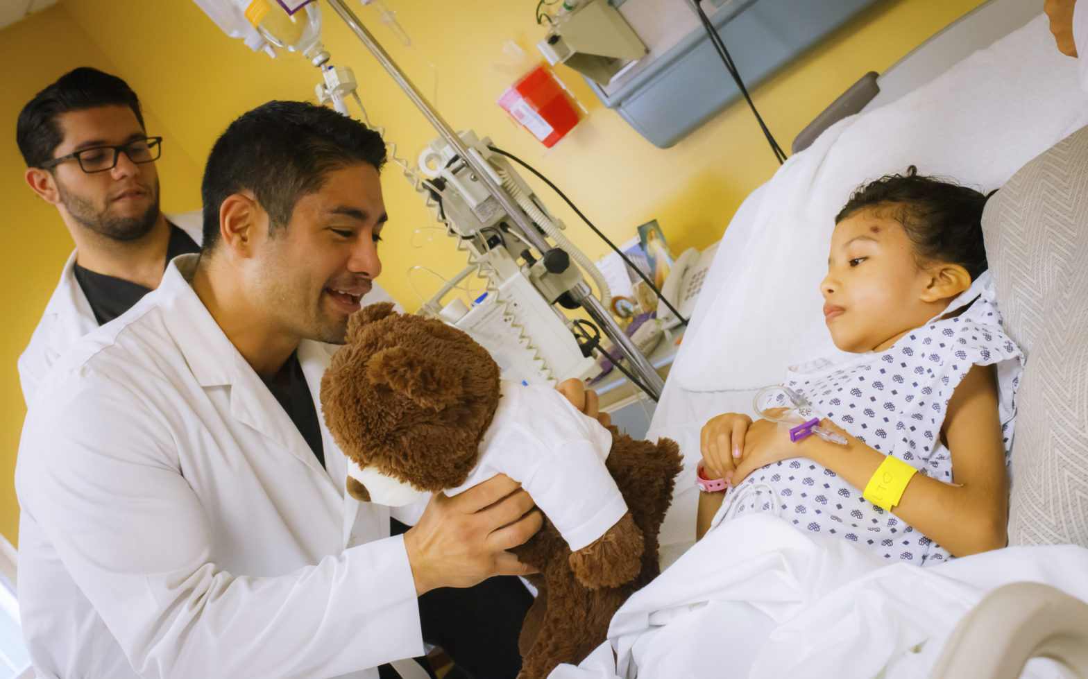 Patient child receiving teddy bear from doctor